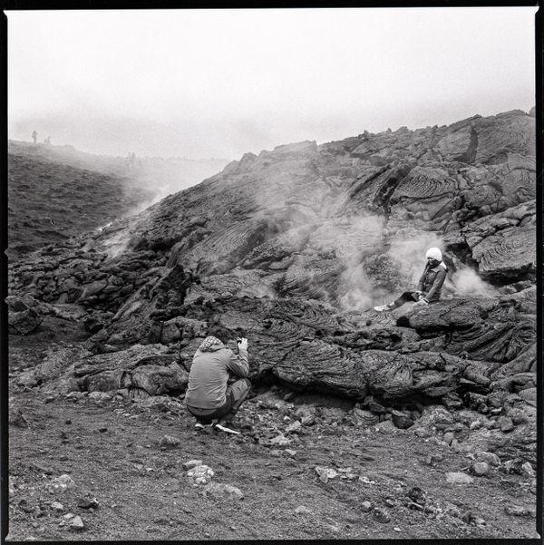 Couple taking photos on smoldering lava thumbnail
