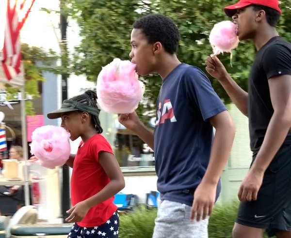 Patriotic siblings enjoy cotton candy during Independence Day Fest. thumbnail