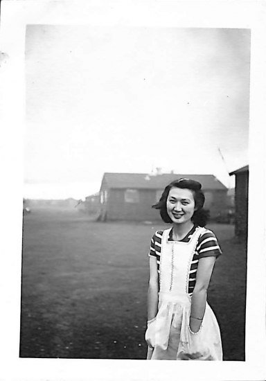 Black and white photo of young woman in white dress and striped shirt