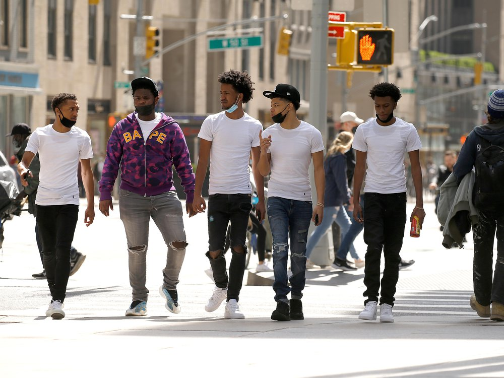 A group of men wearing protective masks walk in Midtown on April 10, 2021 in New York City.