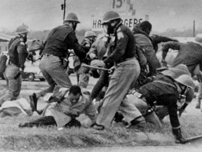 An Alabama State Trooper swings his baton at the head of the then-25-year-old Congressman John Lewis on March 7, 1965.