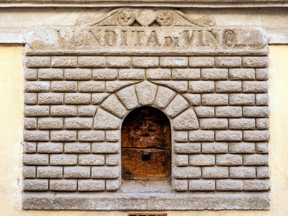 """A small door cut into the side of a house. The door has engraved stone around its entrance, made to look like a tiny building facade. It bears an inscription that has worn away, but includes the word """"VINO"""""""