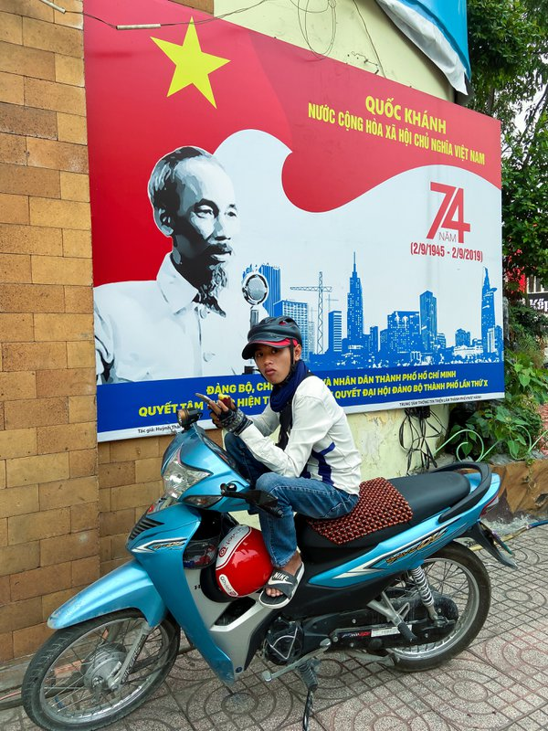 A young Vietnamese parks his motorcycle in front of a poster of revolutionary leader Ho Chi Minh thumbnail