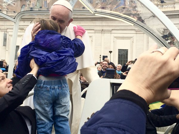A child is lifted up by Pope Francis' security detail for a kiss and blessing from the Pope himself. thumbnail