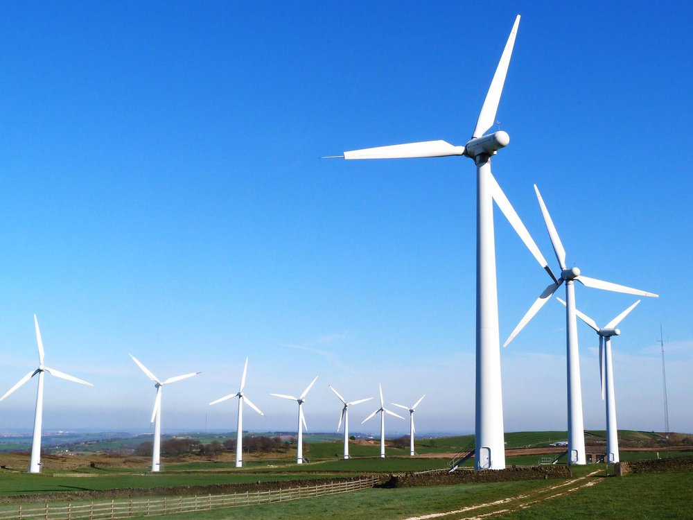 Ten tall, white wind turbines organized in two rows in a grassy field. The sky is bright blue in the background.