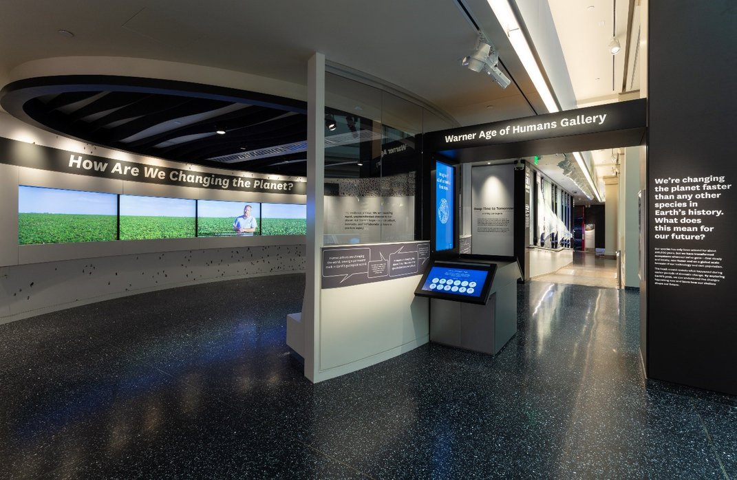 """Small theater featuring four screens and """"How Are We Changing the Planet?"""" in white on a black wall at the Smithsonian's National Museum of Natural History"""