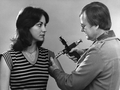 This 1976 photograph shows a woman receiving a vaccination during the nationwide swine flu vaccination campaign.