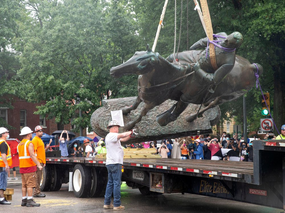 A group of people in hard hats, some in orange work vests, guide a large statue of a bearded man on a horse onto a truck's platform. The statue is dark gray larger-than-life, suspended by a rope and a crane (out of view); many onlookers watch nearby