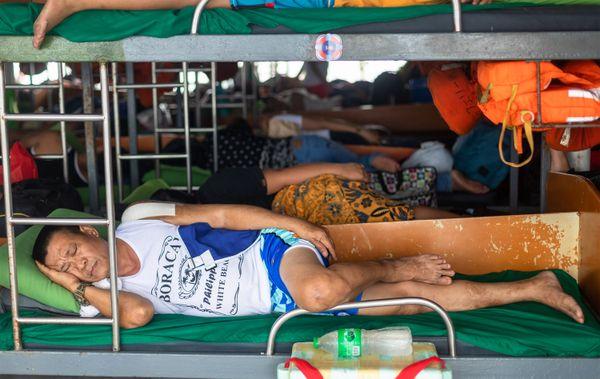 A man sleeps at the lower bunk of a passenger ship thumbnail