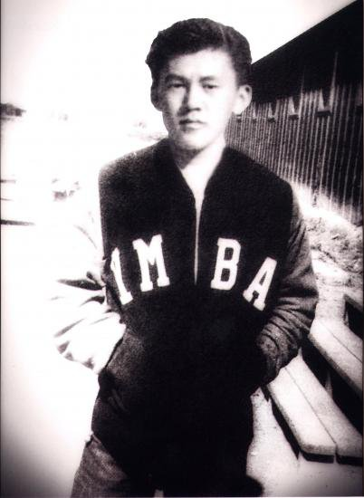 Black and white photo of Testuo Furukawa in YMBA letterman jacket
