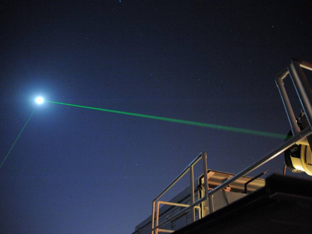 A dark night sky with some metal equipment and beams in the foreground, and then a bright green line shooting through the sky toward a bright full white moon