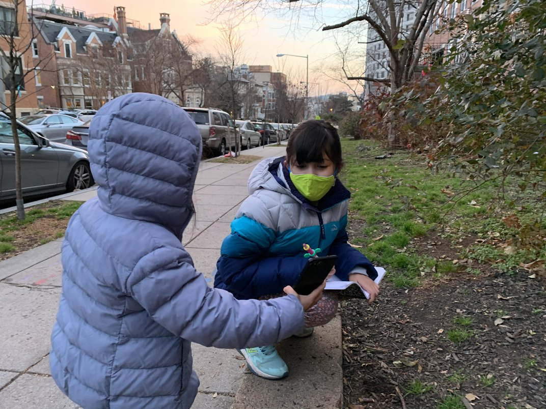 Two kids using a notebook and cell phone while outside.