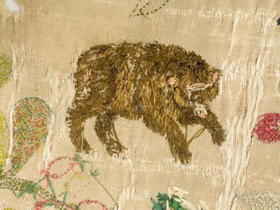 The cloth is embroidered with animals, plants and narrative scenes