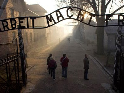 """A focal point for visitors today, the gateway sign says """"Work Will Set You Free,"""" a monstrous lie told to the men, women and children imprisoned there."""