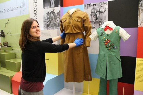Curator removing two dresses from forms in an exhibition