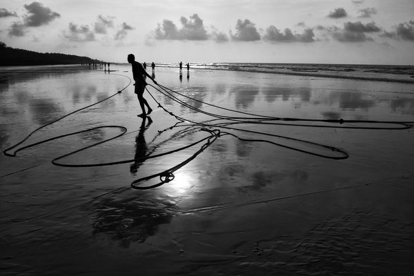 After a hard nights work in the sea, a fisherman packs up, collecting the rope which ties the nets. thumbnail