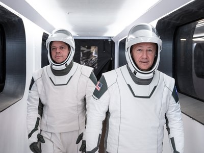 Astronauts Bob Behnken and Doug Hurley walk through Crew Access Arm in SpaceX spacesuits during a dress rehearsal for the first crewed SpaceX launch.