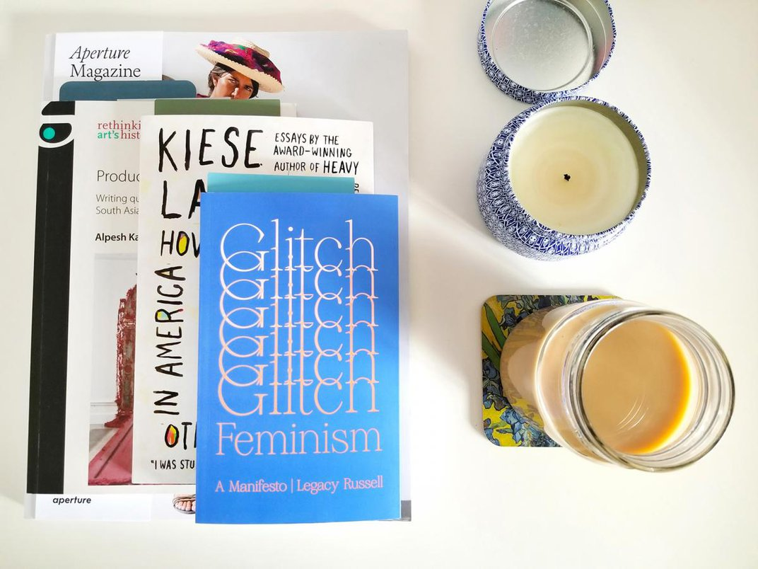 A photograph of books and a candle