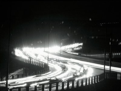 """Ribbons of light slash through the darkness that is New York City during the Giant power Failure November (th. The """"ribbons"""" are formed by the lights of vehicles moving along a highway."""