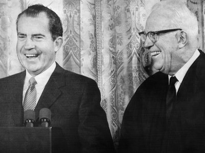 President Richard Nixon smiles alongside Chief Justice of the United States Earl Warren, even though the two waged political war against each other for decades