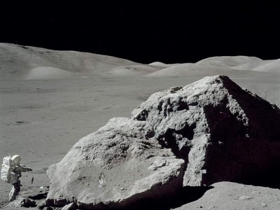 Jack Schmitt picking up the gnomon after collecting samples. This view is to the west toward the Lee Lincoln Scarp. Apollo image AS17-140-21496.