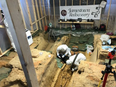 Scientists don full-body suits to minimize contamination and disturbance of the precious artifacts uncovered in the 1617 church in Jamestown, Virginia, where a new skeleton awaits identification.