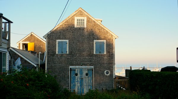 A Cape Cod fishing shack with sailboats in Provincetown Harbor, MA. thumbnail
