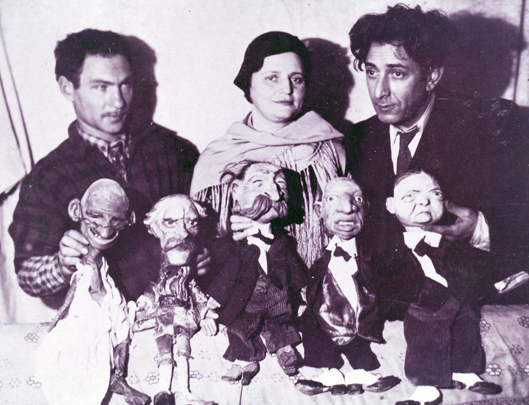 Two men and a woman stand in the background of the photo. They each hold handmade puppets of political figures