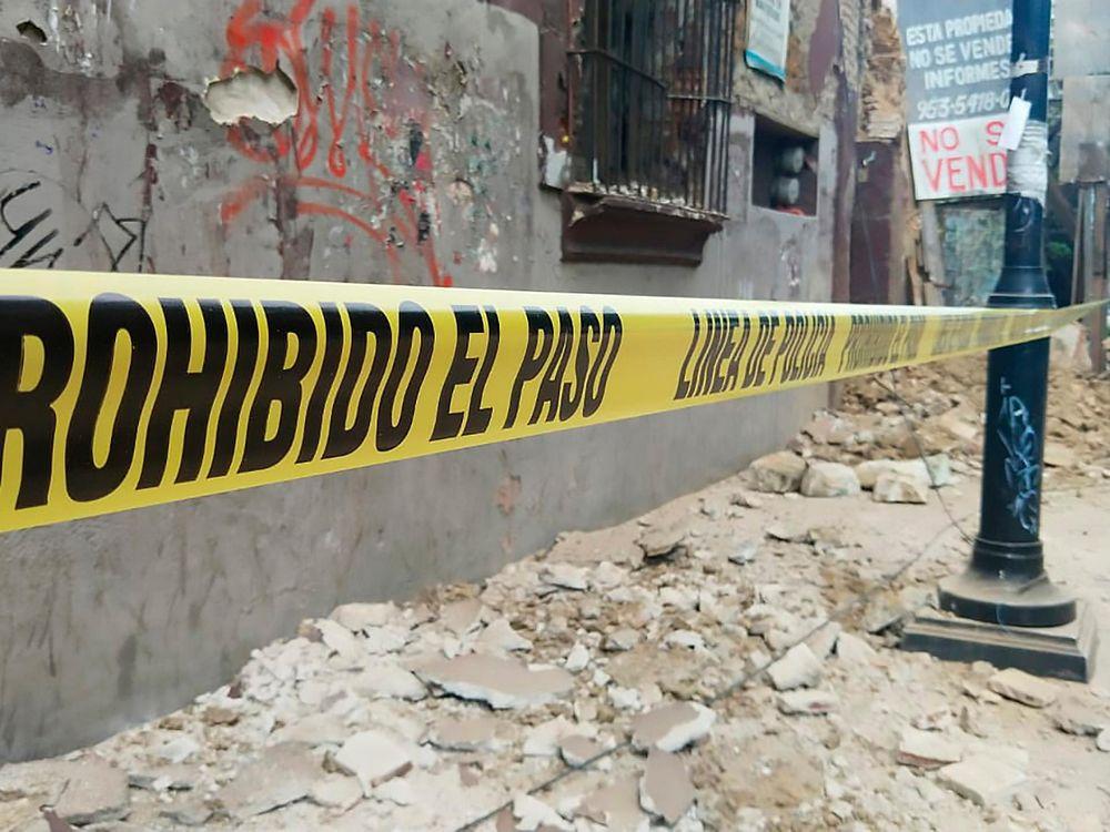 """Debris covers a street in Oaxaca. Caution tape reads """"Prohibido el paso - linea de policia"""""""