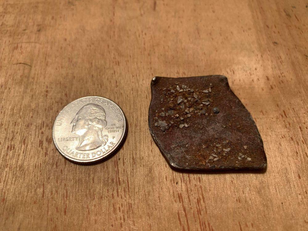 Shipwreck coin next to quarter