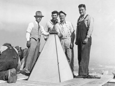 Man posing with construction workers at the top of the Washington Monument. The first restoration of the Monument began in 1934 as a Depression-era public works project.
