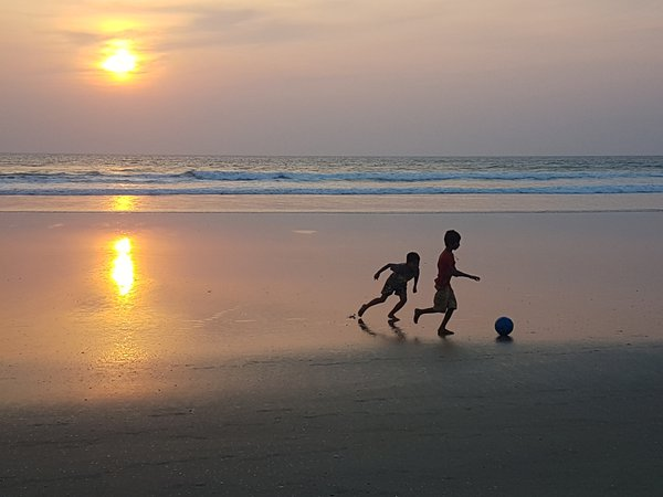 Children playing football in the beach while roaming in the beach thumbnail