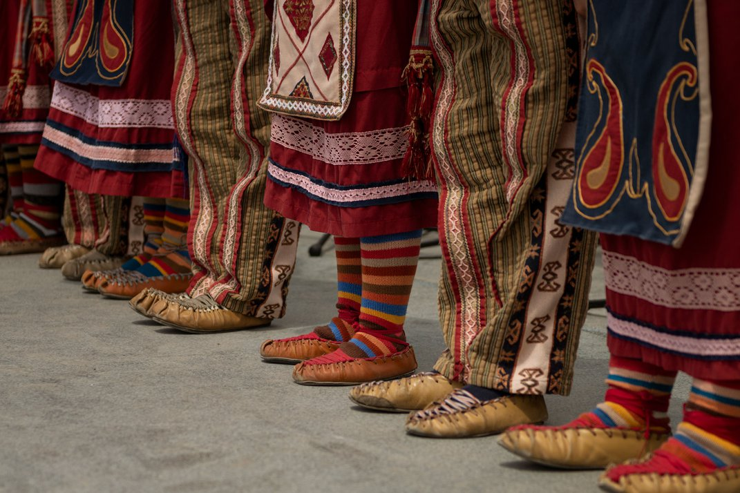People wearing traditional, Armenian shoes with brightly colored pants and socks stand in a line. They are pictured from the waist down.
