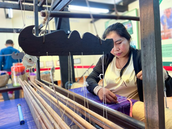 A Cambodian weaves textile using a handloom machine thumbnail