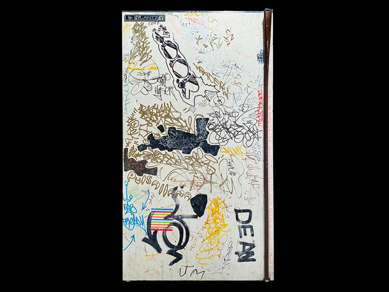 A white refrigerator door covered in scribbles, multicolored graffiti tags, signatures, cartoons, and more