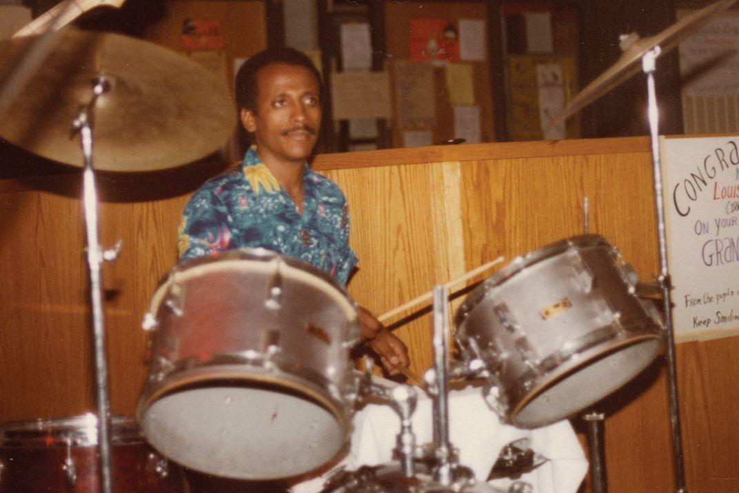 Drummer behind a silver drum kit.