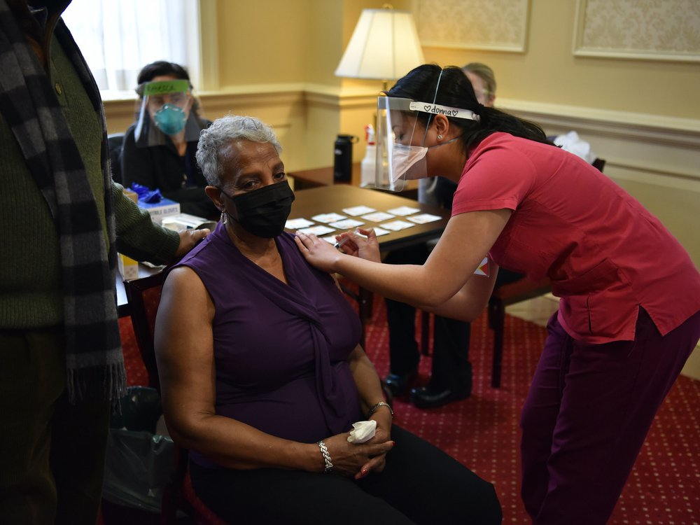 A woman sits in a chair and gets a vaccine shot from a woman wearing a face mask and shield