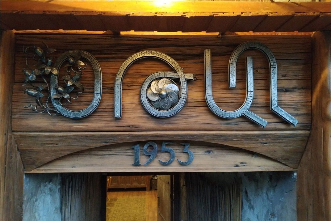 The top of a wooden entryway is heavily decorated with found-metal sculpture, greeting visitors.