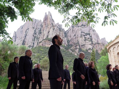 Several men and women dressed in all black, standing in formation with a towering stone mountain behind them.
