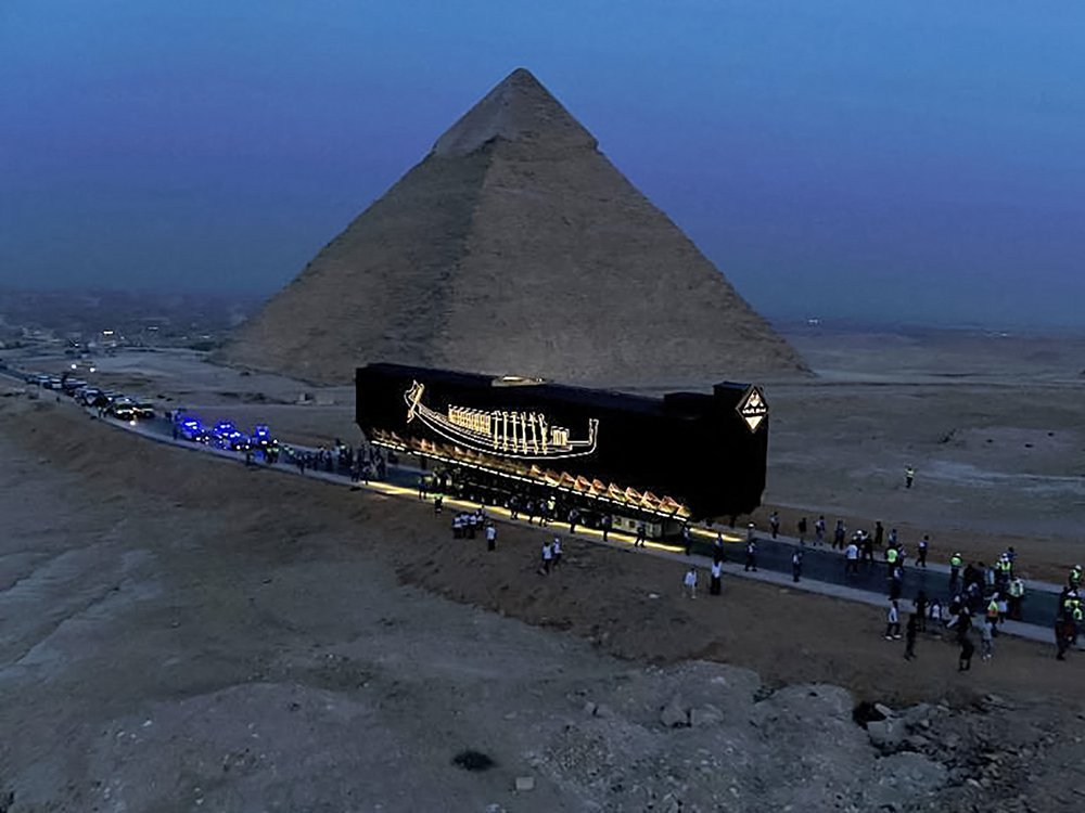 View of boat being moved past Pyramids of Giza