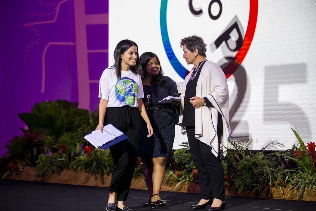 three women meet on stage