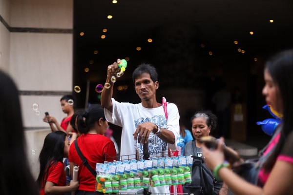 A male vendor sells bubble machines at Chinatown thumbnail