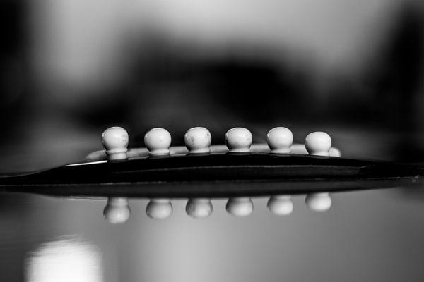 View of bridge and bridge pins of a guitar thumbnail