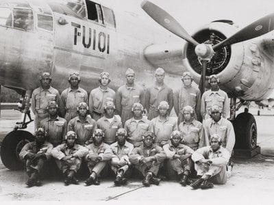 Men of the all-African American 477th Bombardment Group pose in front of a North American B-25 Mitchell.