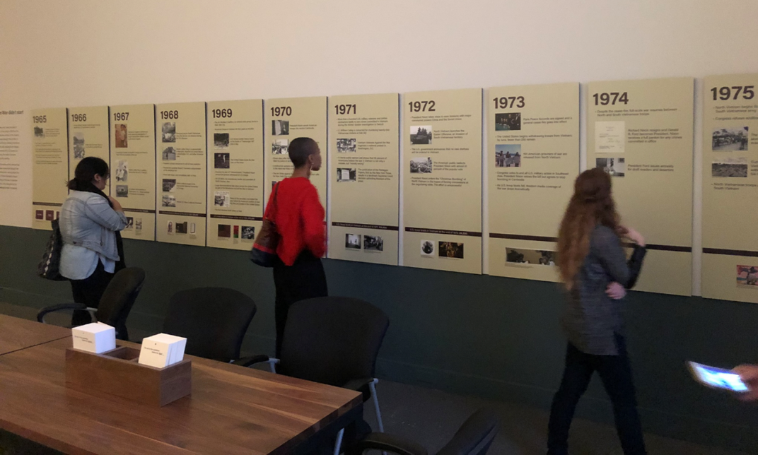 A photograph of people in a museum looking at a timeline wall.