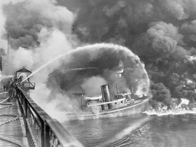 Original Caption: Firemen stand on a bridge over the Cuyahoga River to spray water on the tug Arizona, as a fire, started in an oil slick on the river, sweeps the docks at the Great Lakes Towing Company site in Cleveland Nov., 1st. The blaze destroyed three tugs, three buildings, and the ship repair yards.