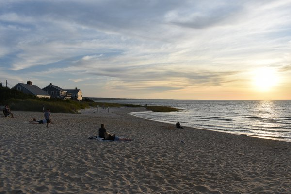 People resting on the sand at Skaket Beach just before dusk thumbnail