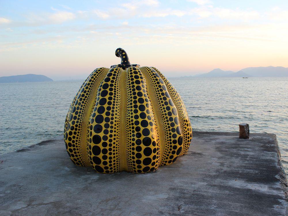 Yayoi Kusama Pumpkin sculpture on a pier