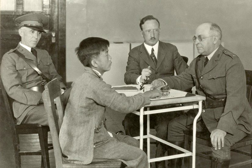 A young Asian man sits at a table with three older white men in uniforms and suits. Black-and-white archival photo.