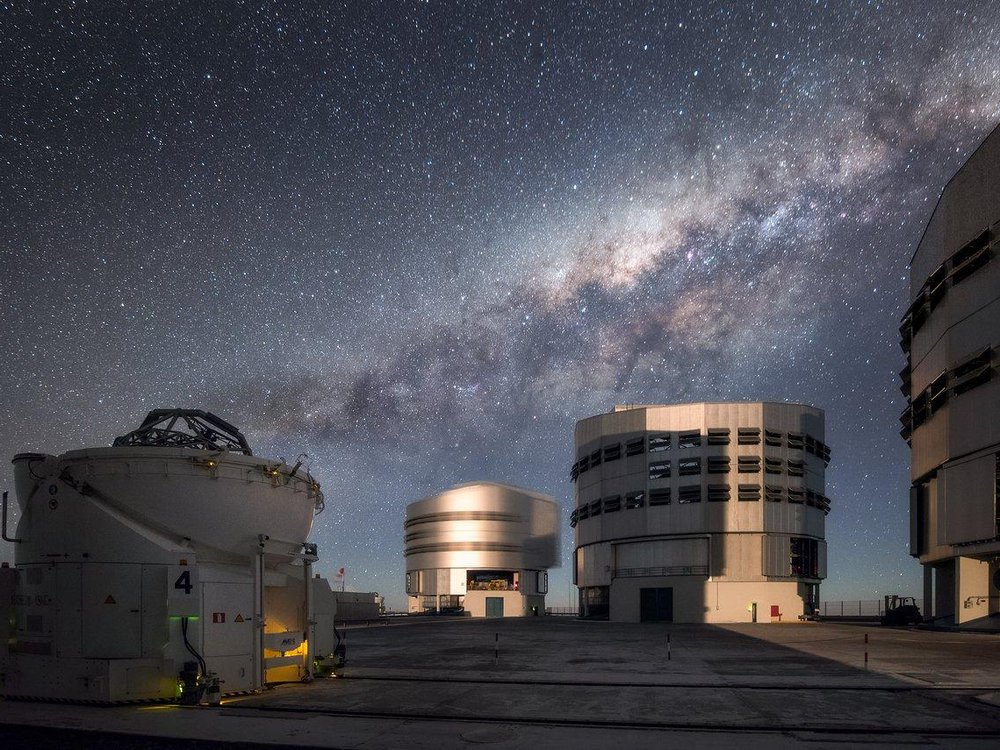 Three of the Very Large Telescope's buildings underneath the Milky Way at night